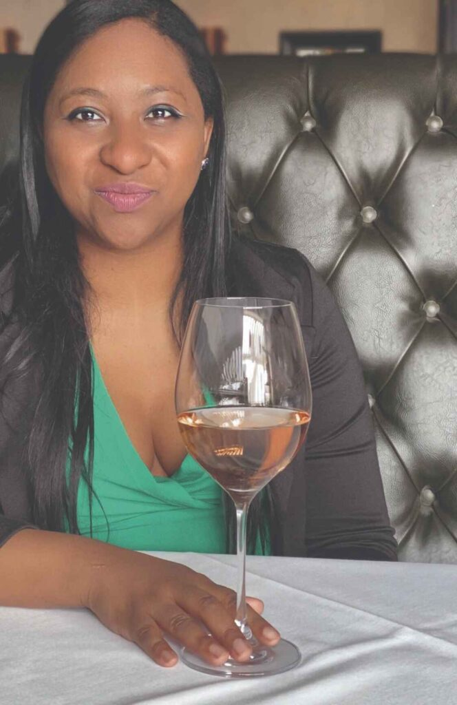 Black woman with long dark hair, green shirt holding a glass of rose wine.