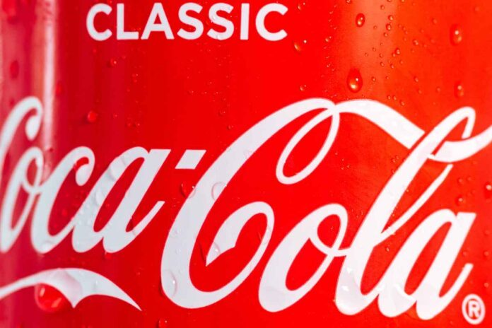 Close-up of red soda can with condensation and white letters reading