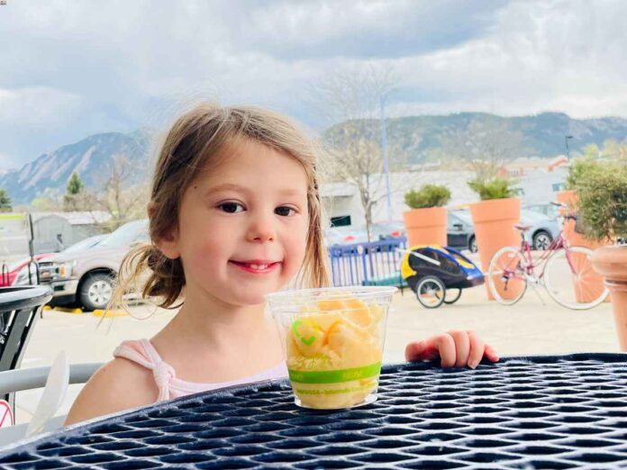 Smiling little white girl with blonde hair sitting at a patio table with a cup of ice cream. Mountains in the background.