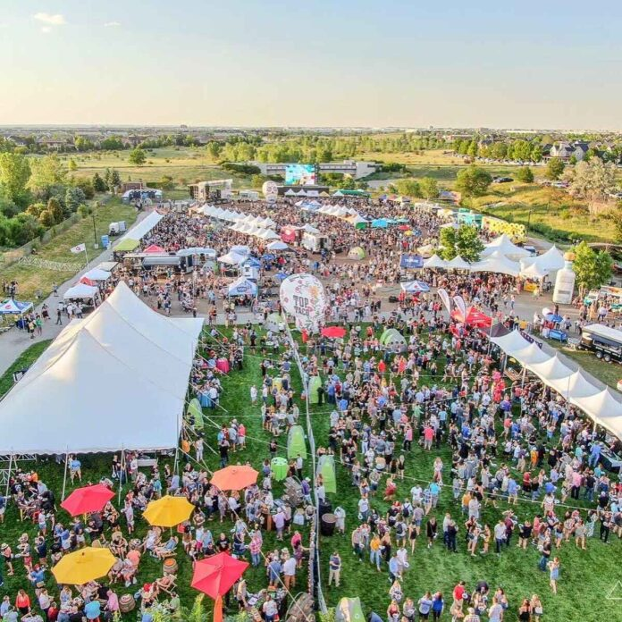 Aerial photo of crowded festival in a field with white, yellow, and red tents, food trucks, banners and many diners. Green trees and clear blue sky are the backdrop.