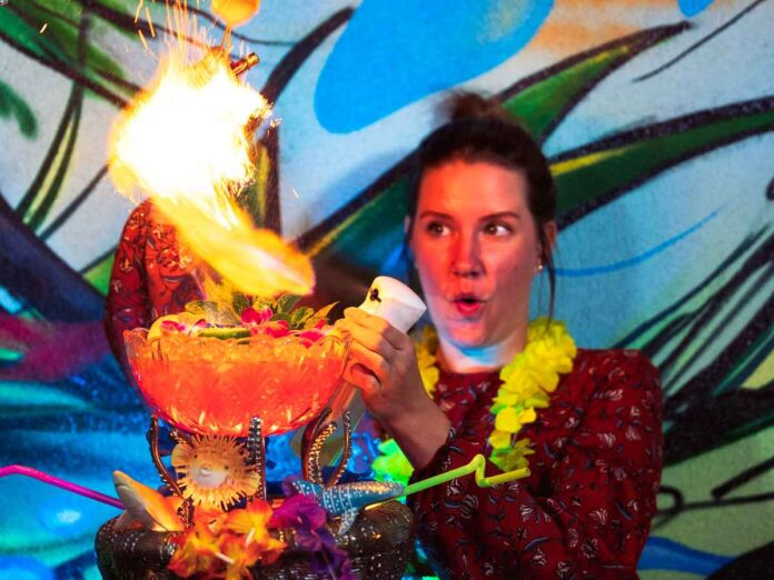 White woman spraying a mist of alcohol over a punch bowl filled with bright orange cocktail and garnished with bright multicolored flowers, straws, and plastic sharks. She's setting the alcohol on fire making an expression of surprise and perhaps fear.