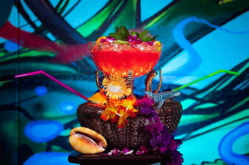 Glass punch bowl filled with bright pinky-orange cocktail and garnished with multicolored flowers, straws, herbs, and plastic sharks. Vibrant tropical blue background and leis, and seashells in the foreground.