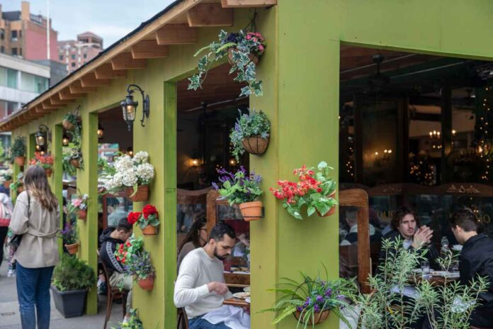 Covered restaurant patio crowded with diners and flowering potted plants.