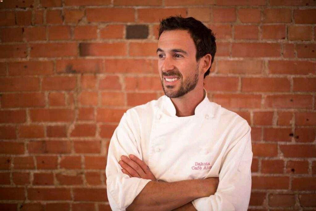 White man with dark hair and beard wearing a chef's coat and standing in front of a brick wall
