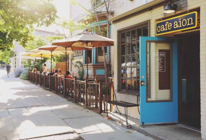 Restaurant with bright blue front door and patio with umbrellas and patio tables along sunny sidewalk.