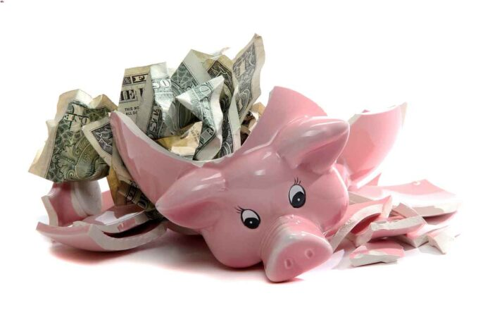 Pink ceramic piggy bank in the shape of a pig broken open with crumpled dollar bills exposed.