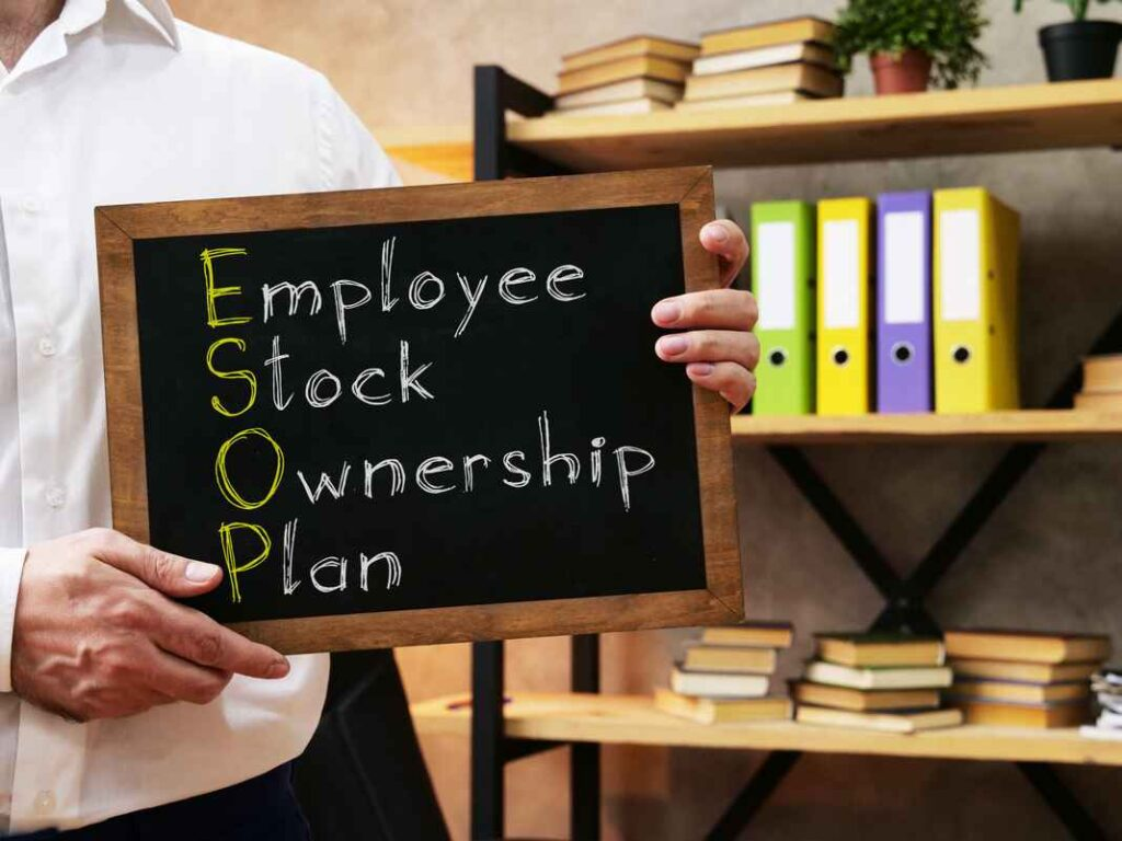 """Man in a white collard shift holding a chalkboard with the words """"Employee Stock Ownership Plan"""" written on it."""