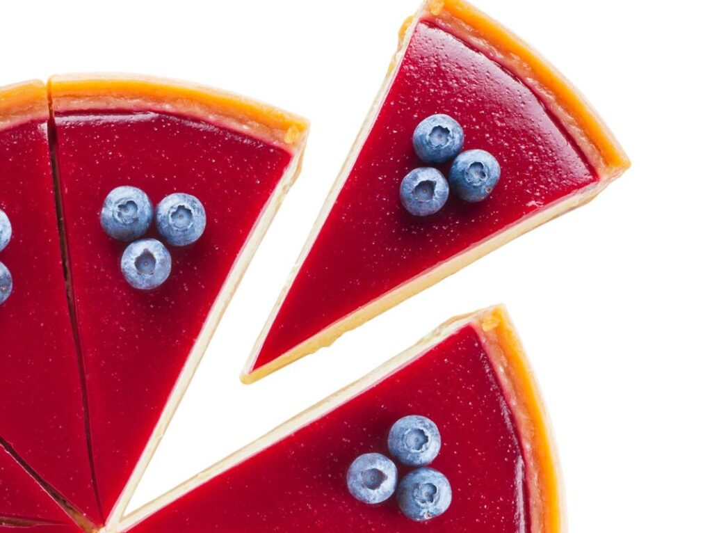 Overhead view of cheesecake with cherry-red glaze and blueberry topping with one slice offset against white background.