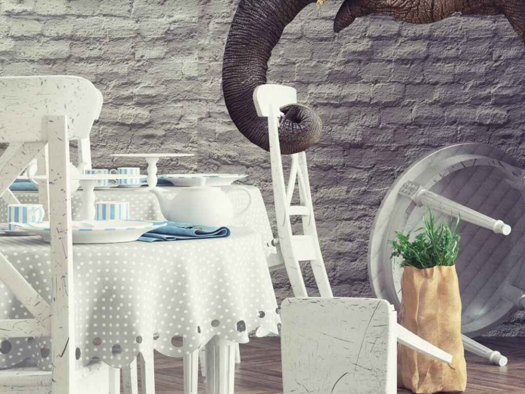Elephant trunk wrapped around the top of a white chair in a restaurant dining room. White tables and chairs are overturned next to tables set with blue and white place settings.