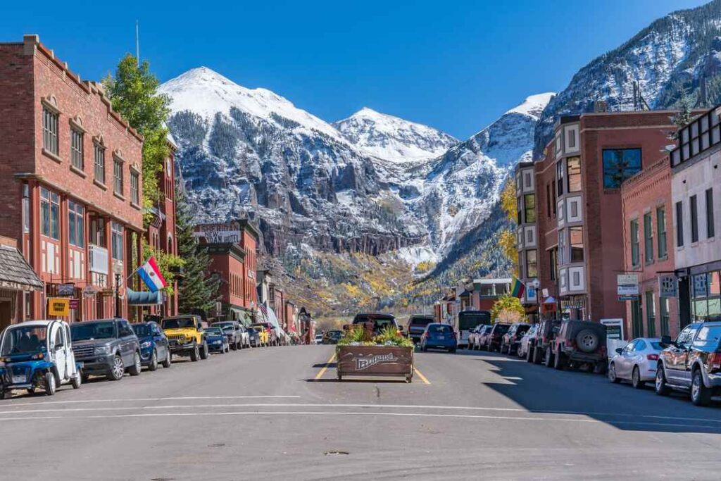 View of a main street in Telluride, Colorado with buildings and cars lining both sides of the street, blue skies and snow-capped mountains in the background.