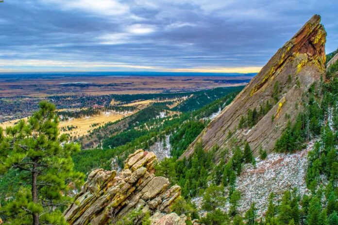View of Boulder, Colorado looking east under cloudy skies, with Flatiron rock formations in the foreground.