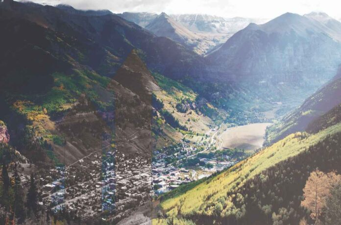 Photo of Telluride, Colorado in a small canyon and its surrounding mountains. Overlay of increasingly tall arrows on the left side of the photo indicating rapid increase in housing costs.
