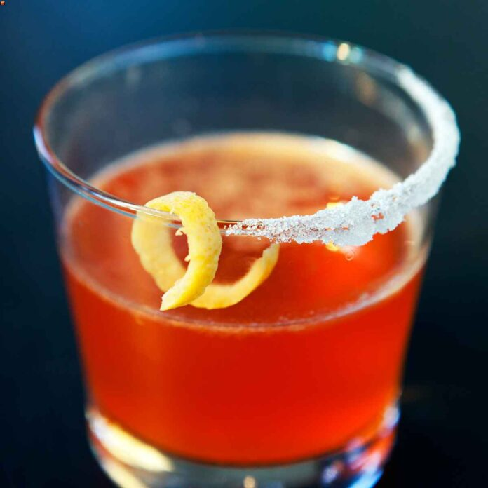 Red-orange cocktail in a glass with salted rim and lemon peel garnish