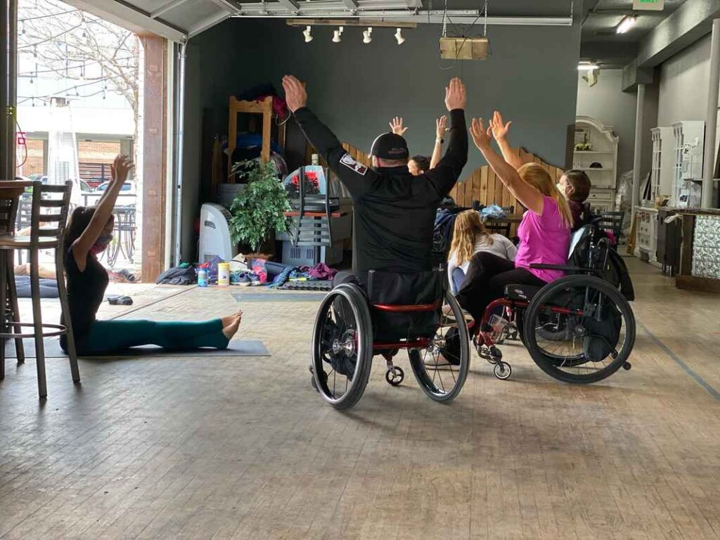 Yoga class taking place inside a brewery. Students are seated on yoga mats on the floor or in wheelchairs with arms raised above their head in a seated yoga pose.