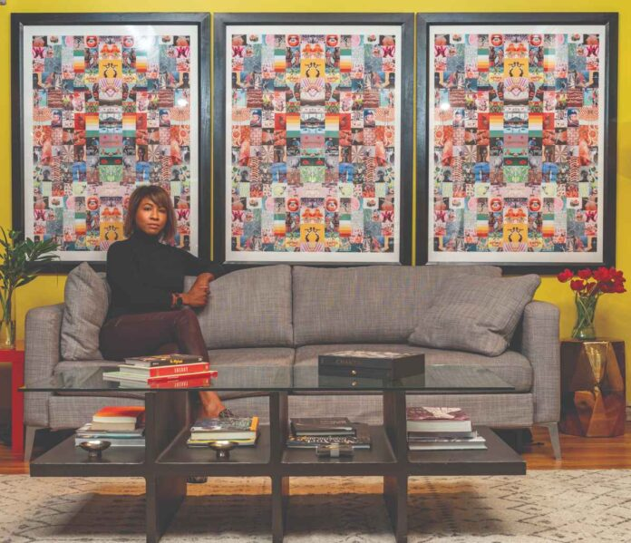 Serious Black woman sitting on a couch against a mustard colored wall with three large, multicored framed art prints.
