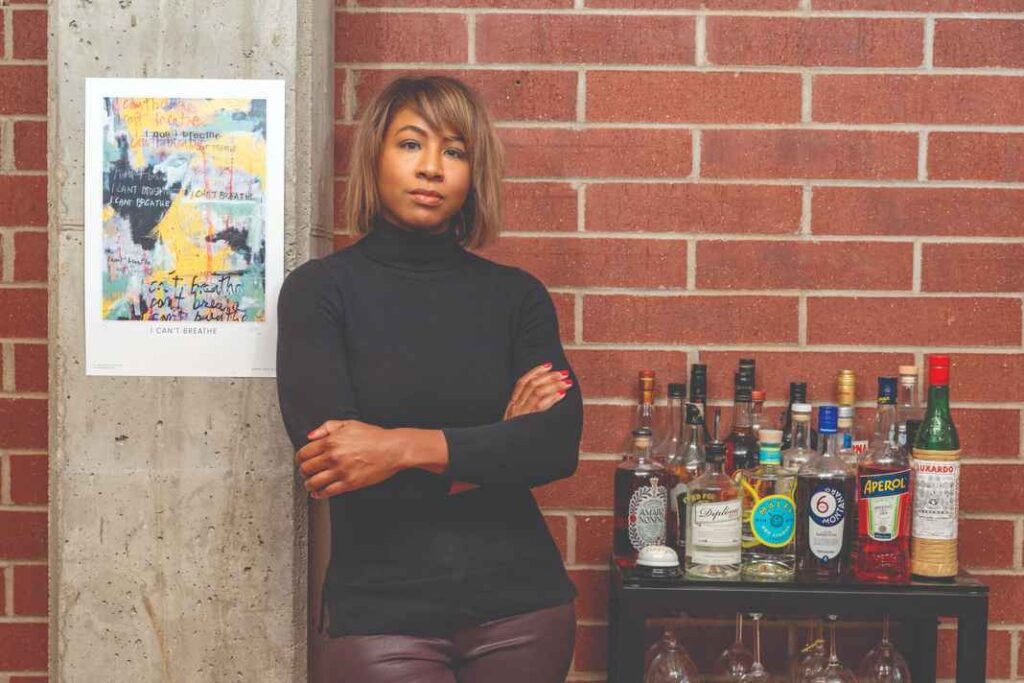 """Serious Black woman wearing a black long sleeved shirt and standing against an interior wall between a bar car with many liquor bottles and a piece of art with the words, """"I can't breathe."""""""