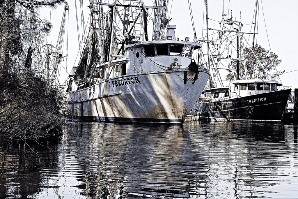 The commercial fishing boat Predator shifts berth, maneuvering in the narrow channel of Swan Quarter, North Carolina.