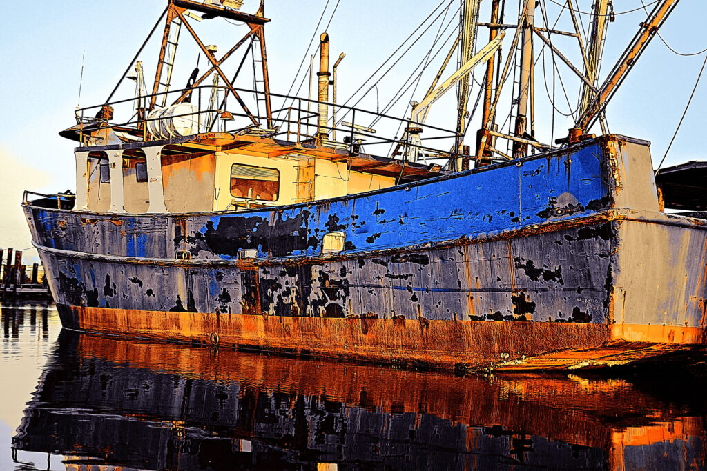 A purse seiner in Swan Quarter, North Carolina, dressed like a rainbow in rust and flaking paint.