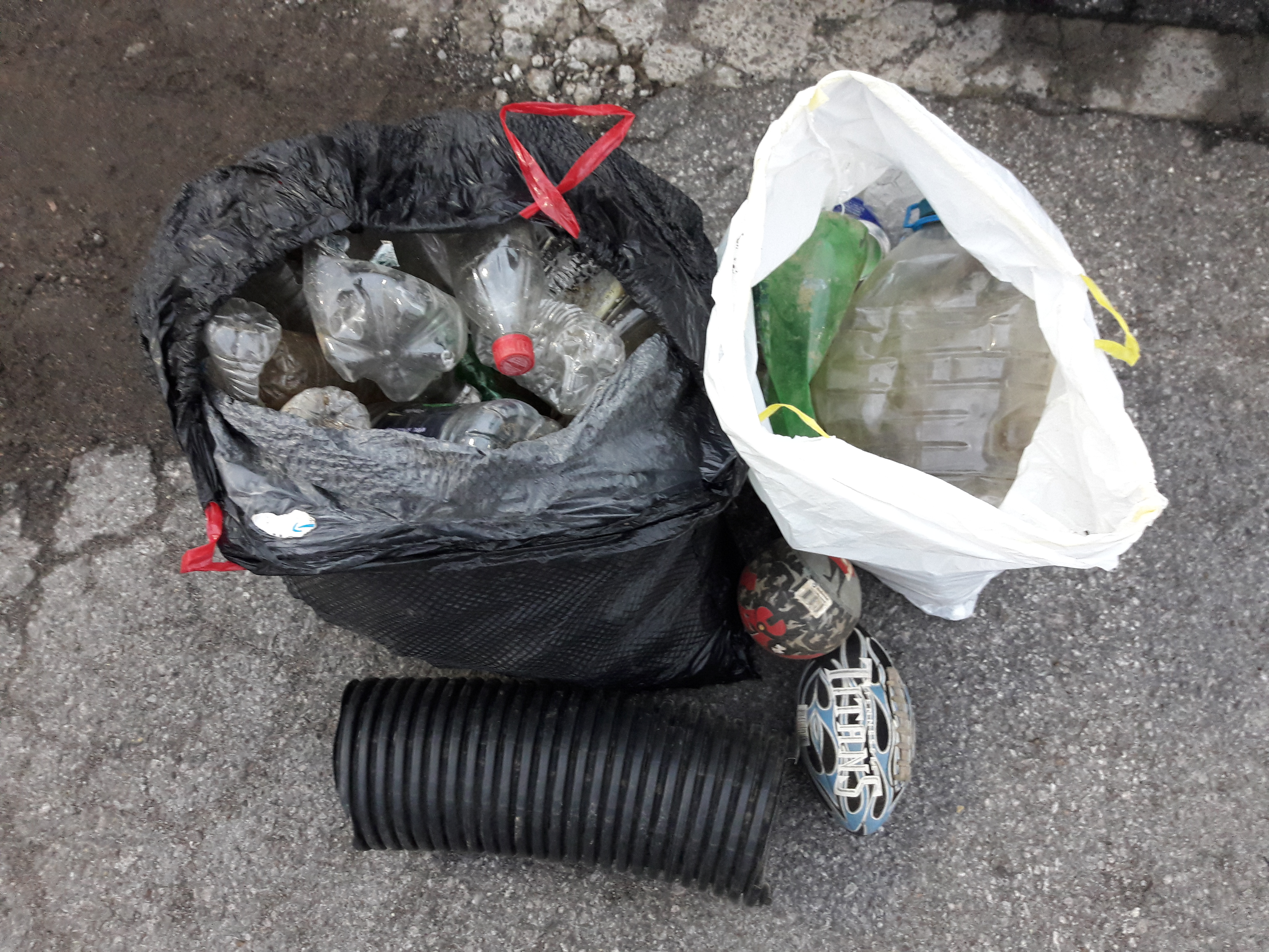 Two small rubber balls and two bags full of disposed cans of beverage, plastic bottles and glass bottles