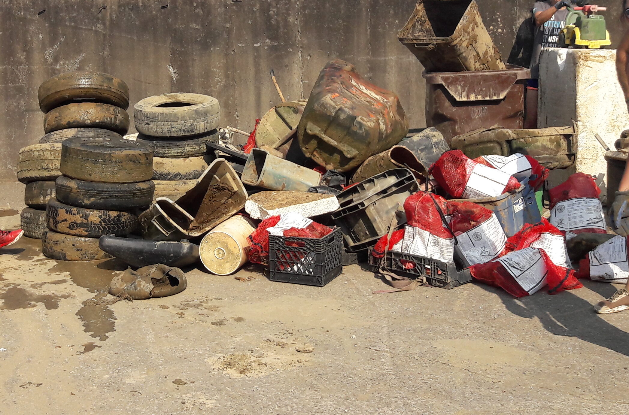 A pile of tires, trash bins, buckets and bags of trash