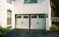 Simple dual overhead residential garage door with arched windows
