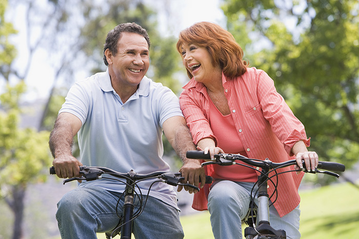 Happy couple riding bikes outside in nature