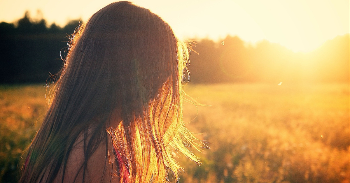 Girl looking over a golden field of sunlight