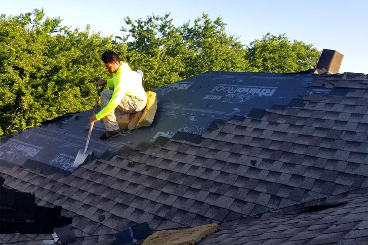 Worker removing shingles from a roof in McKinney TX