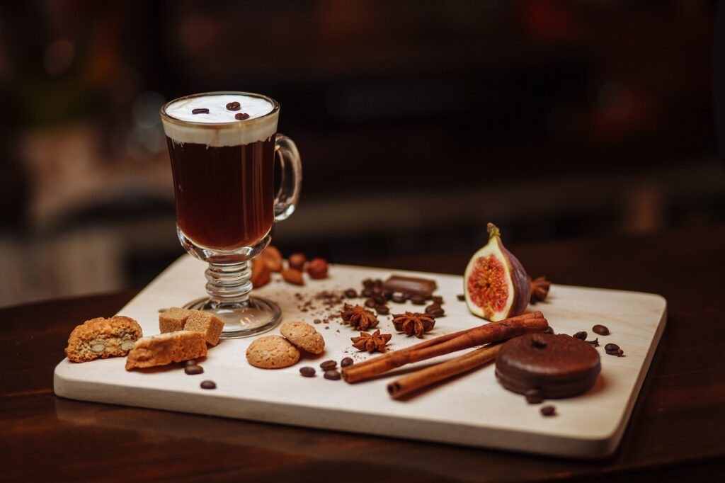 Irish coffee served in the glass cup with garnishing on the side plate