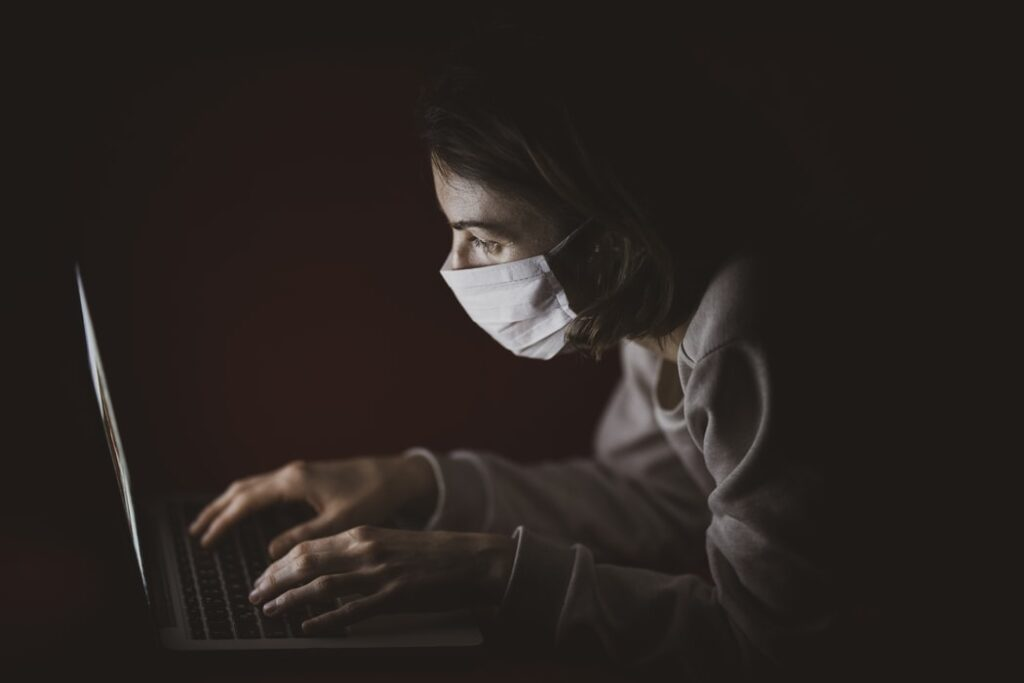 girl wearing mask and working on a laptop