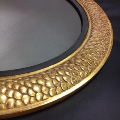 Hand-carved, round mirror designed by Lichten Craig Architecture & Interiors, fabricated entirely at Artmill Group's workrooms. Carved out of basswood, finished in 22k gold over a red bole with a matte black lip. This frame is shown with custom antique mirror.