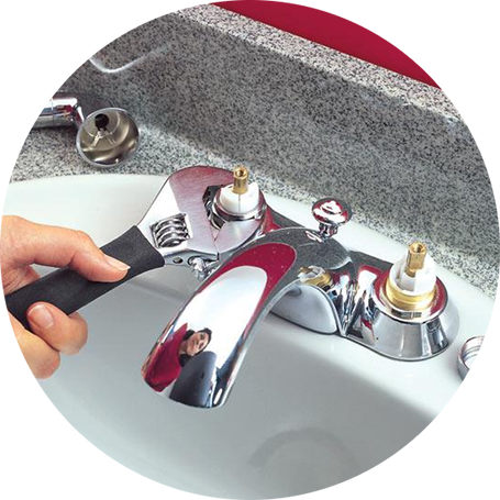 Plumber using a small wrench on a bathroom faucet