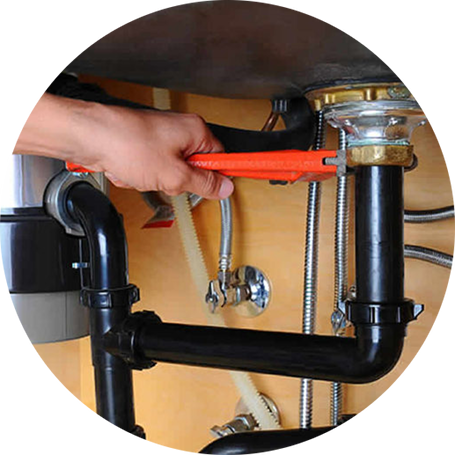 Plumber using a pipe wrench on a garbage disposal beneath the sink