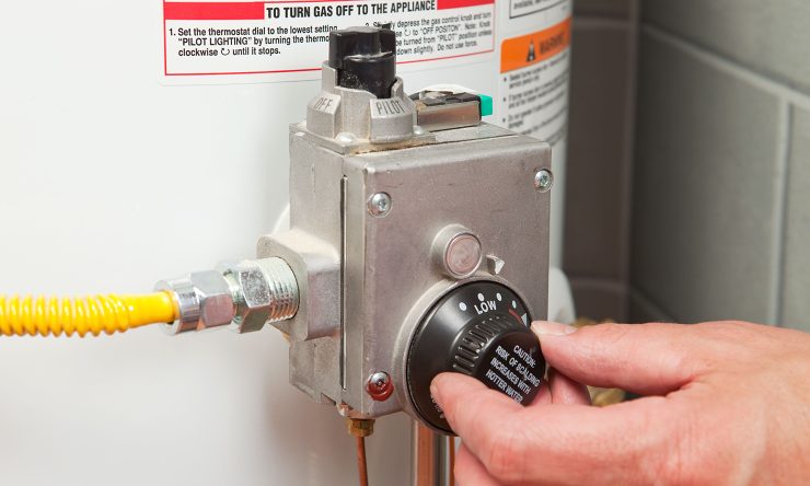 Hand turning a knob on a water heater