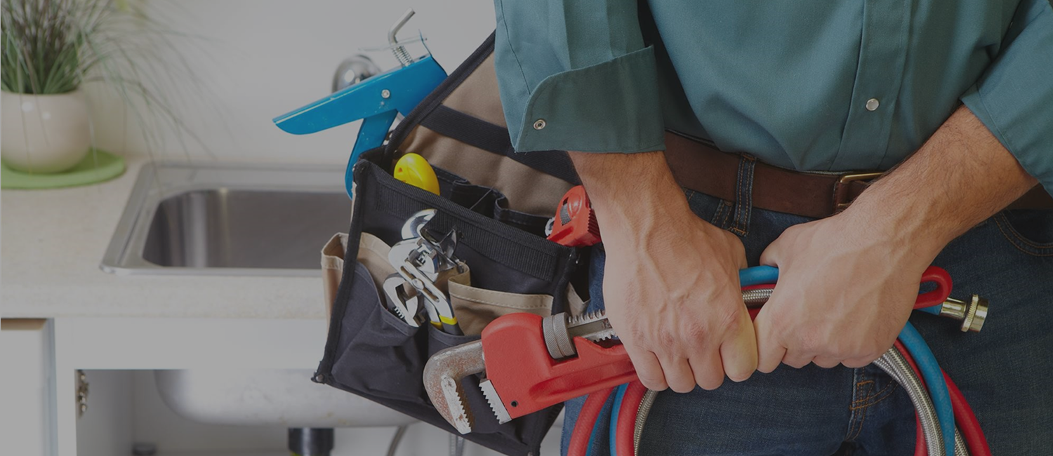 Plumber holding tools and toolbag in kitchen with an opaque black overlay