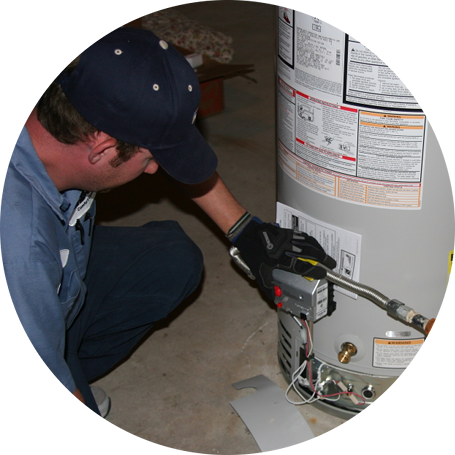 Plumber kneeling to fix a water heater