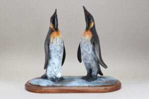Pair of King Penguins celebrating laying an egg