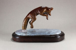 A Bronze Fox jumping for rodent under the snow