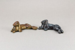 Two little flop eared rabbit sculptures. One is patina'd brown and white, and the other black and white.
