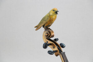 a close up of the Yellow Warbler sitting on a violin neck