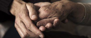 young man holding the hand of elderly parent