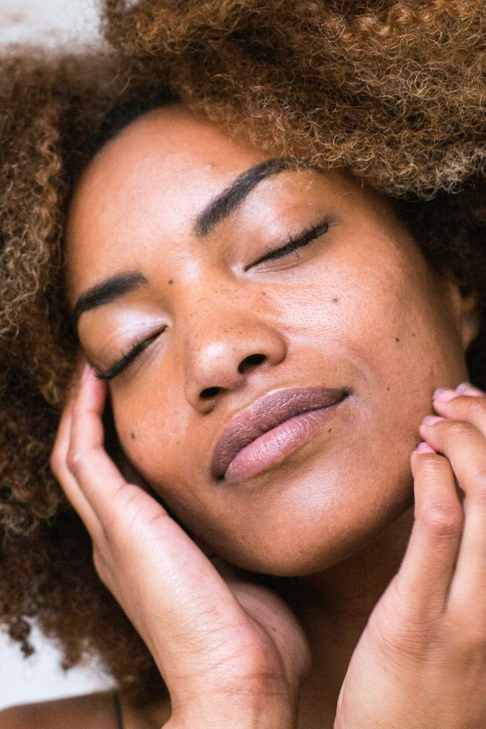Black woman with eyes closed touching her face