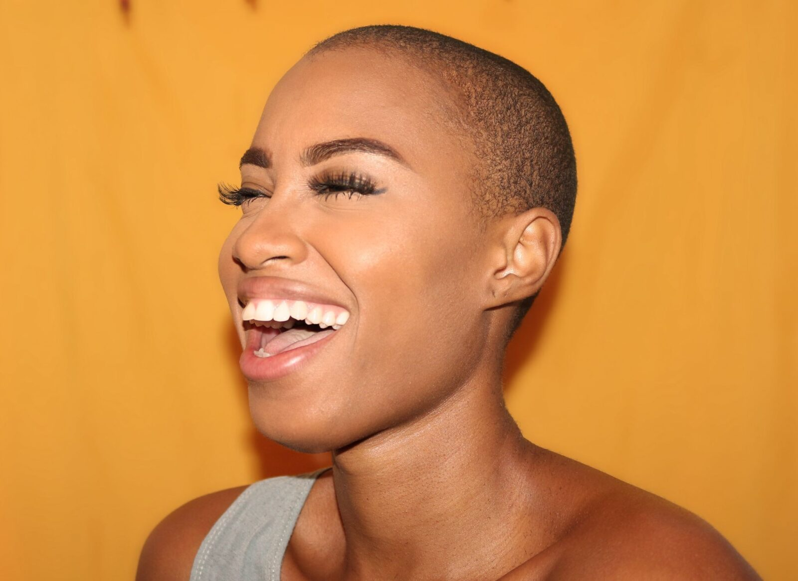 Bald woman on yellow background smiling with mouth open and eyes closed