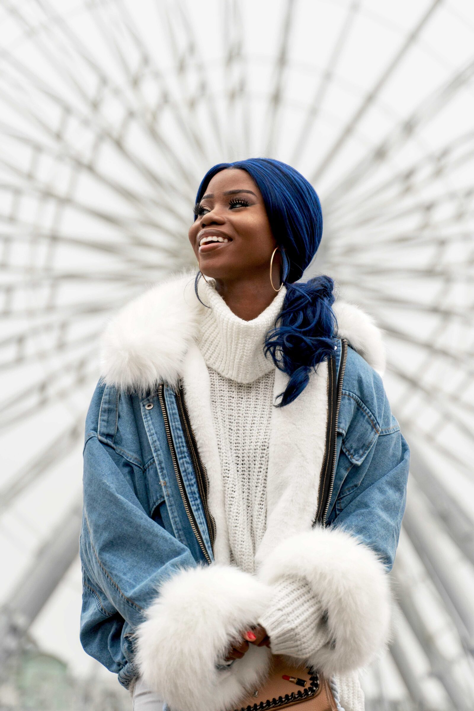 Brown skin girl with wavy deep blue hair and white turtleneck under opened jean jacket against a white background