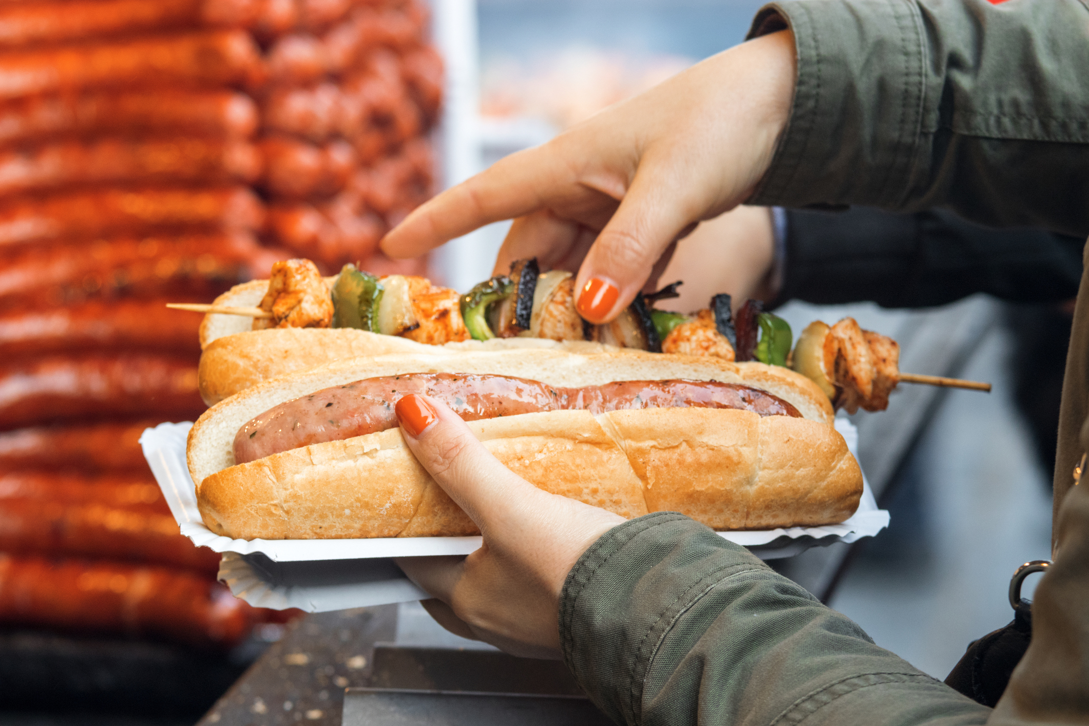 Woman bought her meal at Christmas street market. She holds paper tray in left hand, 2 breads on the tray, one with the sausage and  the other one with kebab skewer. Detail image, focus on 1st bread with sausage.