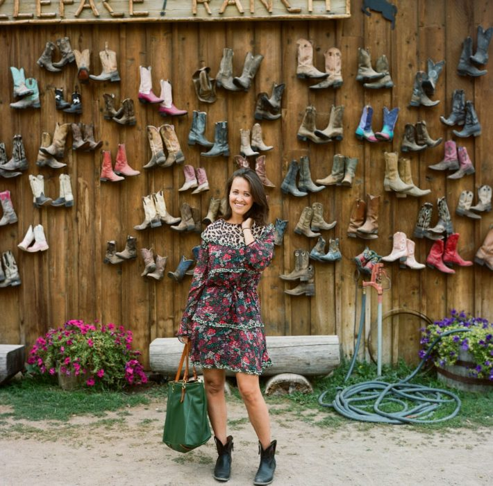 Jackson Hole Style blogger Meagan wearing printed dress from Nest infront of wall of cowboy boots on Puzzleface Ranch