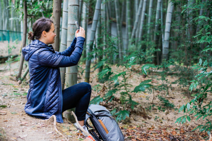 Athleta Rock Springs Jacket on travel blogger taking a photo in the bamboo forests of Kyoto, Japan