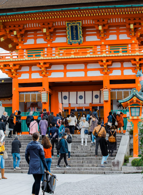 Travel blogger stands in front of Japanese shrine in Kyoto
