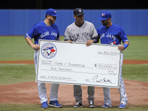 Aug 31, 2014; Toronto, Ontario, CAN;  Toronto Blue Jays players Mark Buehrie (56) and Jose Bautista (19) preset a New York Yankees Derek Jeter (2) check for $10,000 for charity before game at Rogers Centre. Mandatory Credit: Peter Llewellyn-USA TODAY Sports ORG XMIT: USATSI-169386 ORIG FILE ID:  20140831_pjc_lb4_101.JPG