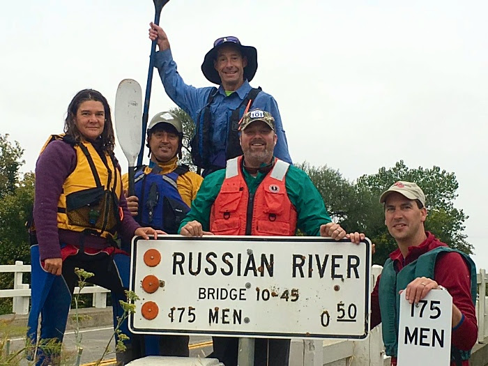 Paddlers posing by Highway 175 bridge sign where they started the day's journey in Hopland on the way to Cloverdale through the roughest section of the River. Meghan Walla-Murphy (trip organizer with Landpaths), Craig Anderson (Director of Landpaths), James Gore (Sonoma Co 4th District Supervisor), Bert Whittaker (Park Operations Manager with Sonoma County Regional Parks) and up top your Riverkeeper Don McEnhill.